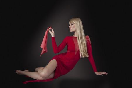 long red hair woman: Fashion model in elegant red dress, dark background