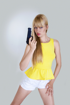 tough woman: Pretty girl in action with hand gun Stock Photo