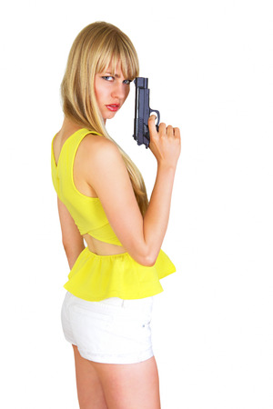 Cute blonde with revolver turning and looking photo