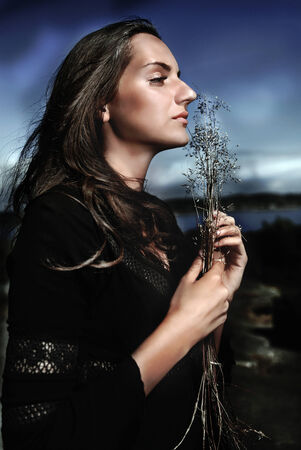 mesmerized: Cult woman by night with dry plant sprig Stock Photo