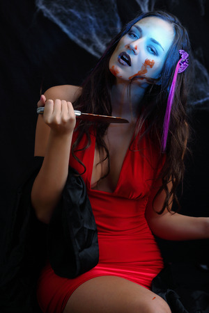 Halloween lady with blood smears and knife photo
