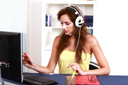concentrating: Cute female busy in home office with computer and headset Stock Photo