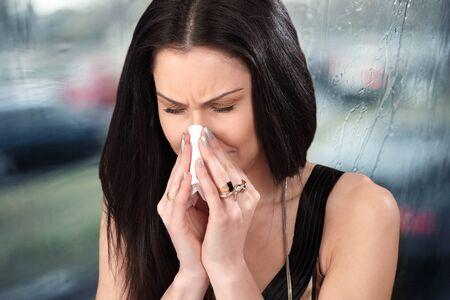 Mujer con frío, estornudos y papel de seda en la temporada de gripe