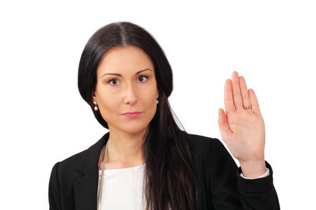 oath: Serious woman makes stop gesture with hand