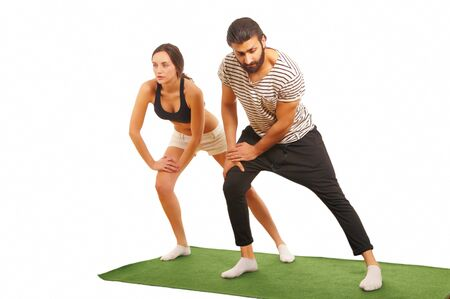 warming up: Athletic couple warming up on exercise mat Stock Photo