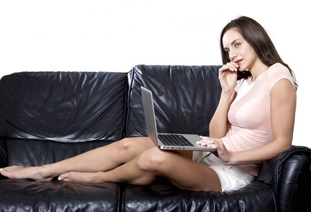 girl with laptop: Thoughtful girl with laptop on a leather sofa