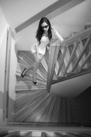 stairwell: Young woman in a stairwell, black and white portrait Stock Photo