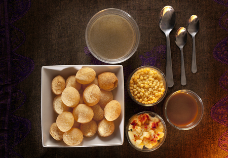 pani: Pani puri or golgappa is an Indian chat or snack item, shown with accompaniments on the side