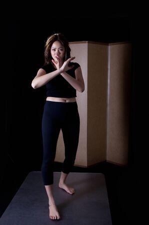 tough woman: Girl practicing martial art, a vertical full body portrait