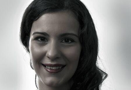 Woman smiling, face closeup in dark tones