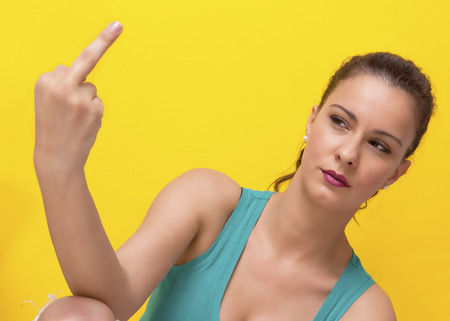 Woman showing middle finger with upset expression