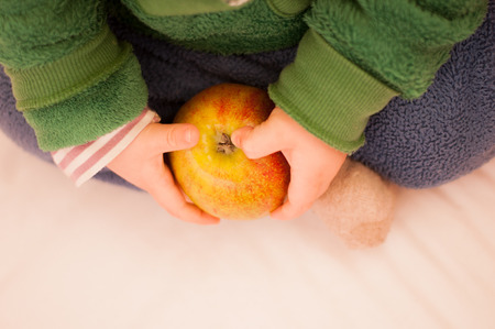 Child holding an apple in a hand. Stok Fotoğraf