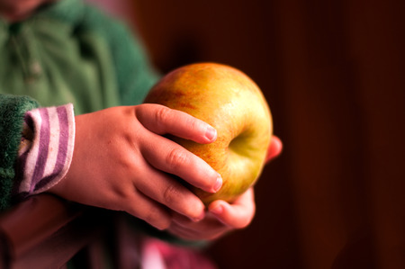 Child holding an apple in a hand. Stock Photo