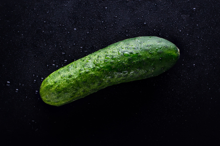 Damp Fresh Green Cucumber On A Black Background With Water Drops. Dark Style. Top View Stock Photo