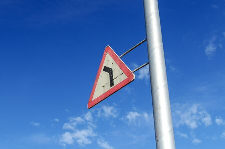peeledoff: The Russian Triangular Road Sign Dangerous Turn With The Peeled-Off Paint Against The Blue Sky
