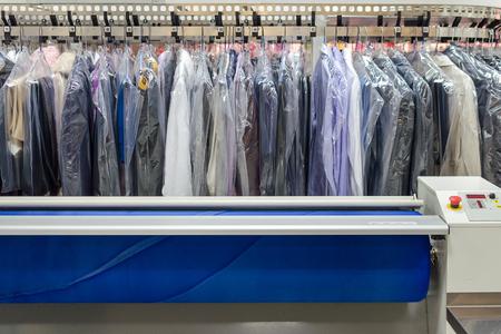 ropa colgada: Ropa Limpia En Perchas en la lavandería industrial Con cilindro caliente Secado planchadora