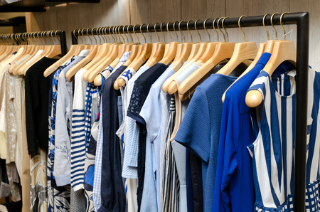 blouses: Multi-Colored Womens Clothing On Wooden Hangers. Blouses, Shirts, Trousers, Jackets. Stock Photo