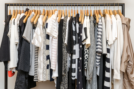 shirts on hangers: Multi-Colored Womens Clothing On Wooden Hangers. Blouses, Shirts, Trousers, Jackets. Stock Photo