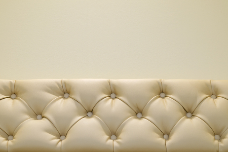 chesterfield: White Leather Upholstery In Chesterfield Style On The Background Wall.