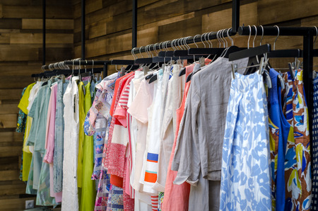 blouses: Multi-Colored Womens Clothing On Black Wooden Hangers. Blouses, Shirts, Trousers, Jackets. Stock Photo