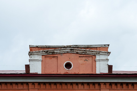 dormitories: The Old Roof House With A Circular Window. Buildings Facade.
