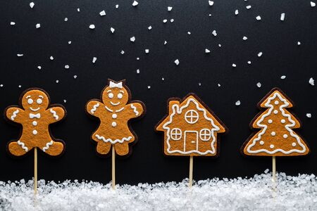 free space: Christmas Background Theme. Ginger Men (Male, Female) In The Snow (Large Sea Salt) Next To The House And Tree. Close-Up. Free Space For Text. Black Background. Top View.