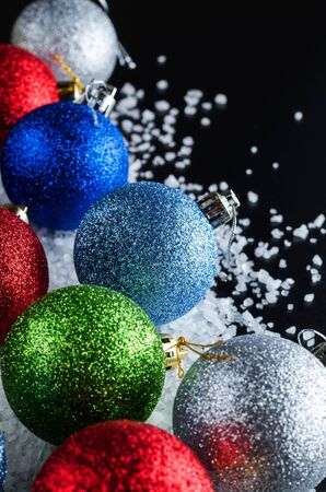 Christmas Background Theme. Multi-Colored Christmas Balls (Red, Blue, Green, Silver, Gold) In The Snow (Large Sea Salt) On A Black Background. Close-Up. Angle View. Stock Photo