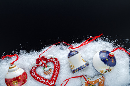 Christmas Tree Decorations (Balls, Bells, Heart, Star) In The Snow On A Black Background. Close-Up. Free Space For Text. Top View. Stock Photo