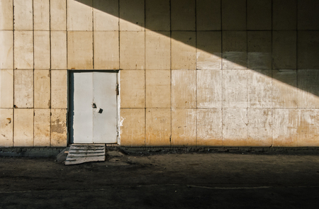 Metal Door In The Wall Of An Old Building At Sunset. Texture, Background Series. Stock Photo