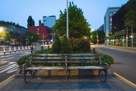 New York, NY - May 16 2020: Long exposure shot of a bench and street in Houston Street in NYC during nighttime