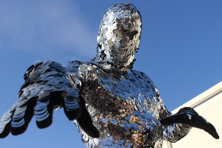 Man covered by shiny silver discs