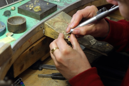 hands working on a gold and silver jewel