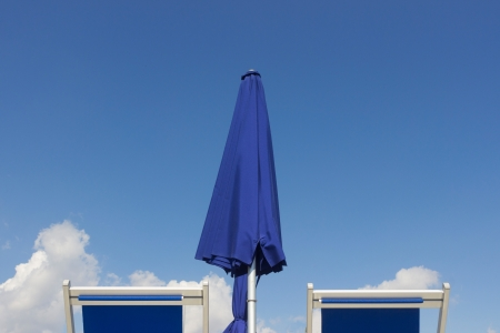 Deck chairs sun umbrella  and blue sky photo