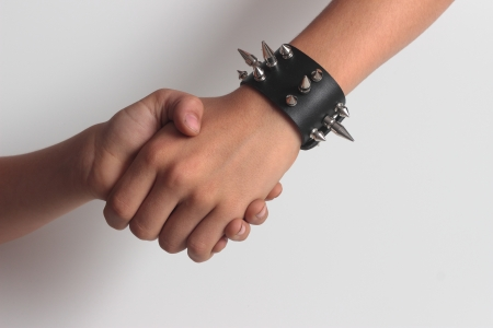 hand shaking with spikes' bracelet photo