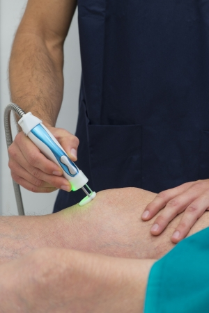 hands on knees: Laser therapy on a knee Stock Photo