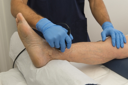 Ultrasound therapy on a foot of an aged man photo