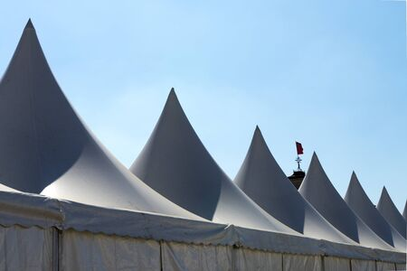 pyramid peak: White tent for events with spier and blue sky Stock Photo