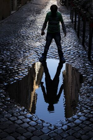 mirroring: Kid mirroring in a puddle