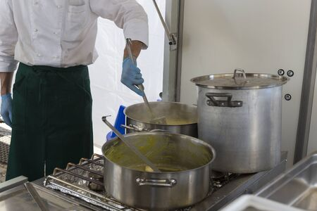 safran: cook stirring risotto milanese with safran