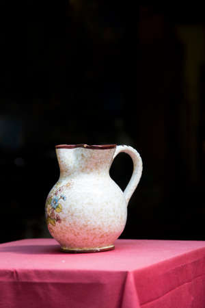 red tablecloth: Jug on the table with red tablecloth