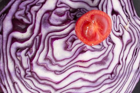red cabbage: Red Tomato on a cutted red cabbage Stock Photo