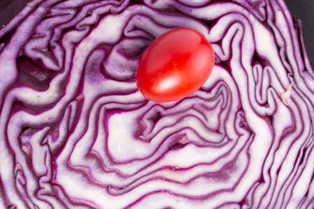 cutted: Red Tomato on a cutted red cabbage Stock Photo