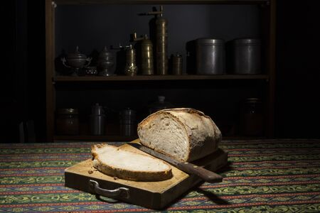 atmosphere: Loaf and slice of italian bread in a cutting board in a dark kitchen