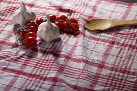 Tomato, garlic and spoon on a tablecloth with copy space Stock fotó