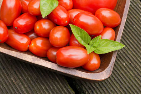 floorboards: Tomatoes With Basil In A Wooden Bowl On Floor Boards Stock Photo