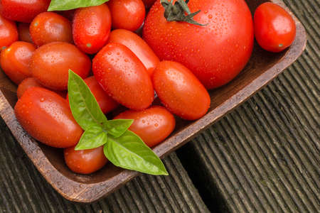 floorboards: Tomatoes With Water Drops In A Wooden Bowl Stock Photo