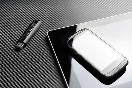 telework: Blank Smartphone With Reflection Lying On Business Tablet Next To An USB Storage Flash Drive Above A Carbon Background
