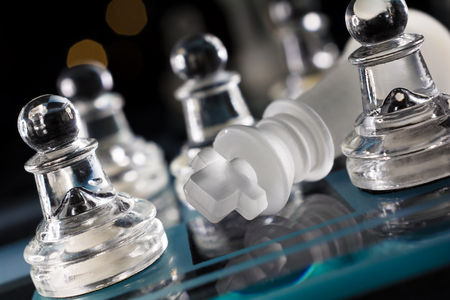 overthrown: Overthrown King On Blue Chessboard With Crooked Angle And Bokeh Stock Photo