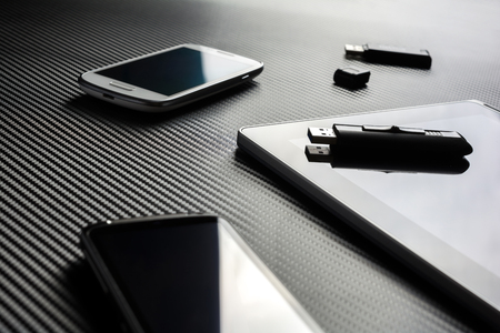 usb drive: 2 Business Mobiles With Reflections And An USB Drive Lying Next To A Blank Tablet With An USB Drive On Top, All Above A Carbon Layer