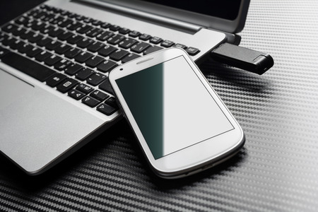 plugged in: Blank White Phone With Green Reflection Leaning On A Business Notebook Keyboard Next To A Plugged In USB Storage Flash Drive, All Above A Carbon Layer Stock Photo